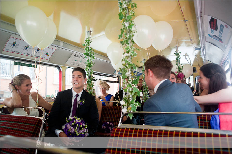 Bride and groom in red Routemaster bus with wedding guests from Westminster Register Office, Marylebone