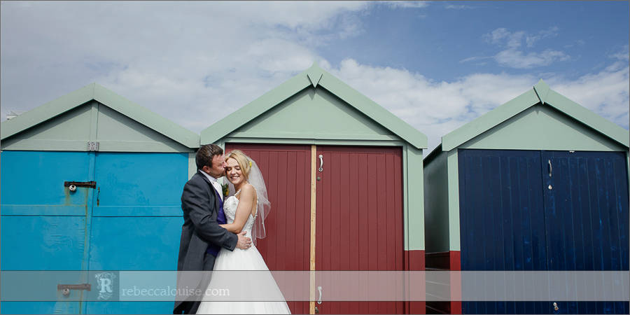 Brighton bride and groom wedding portraits with beach huts on sunny day