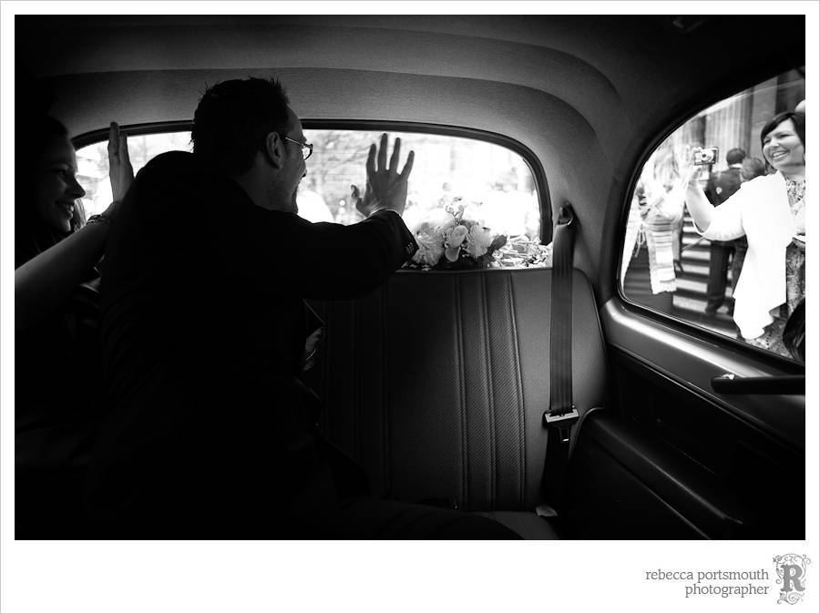Bride and groom wave goodbye to guests from a white cab