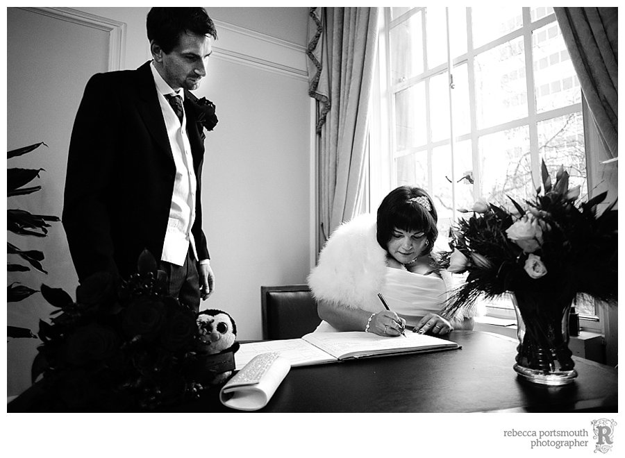 Karen and Matthew sign the wedding register in Westminster's Yellow Room.