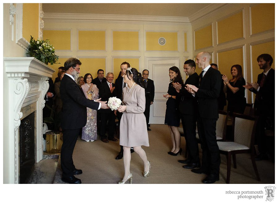 Bride Emine and groom Richard walk into their civil wedding ceremony at Westminster's Yellow Room - 2013