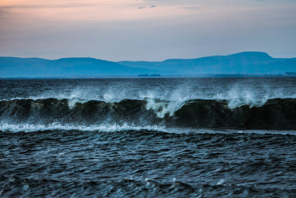 Breaking waves along Findhorn Beach. Life has it's own momentum. Surfing is a skill.