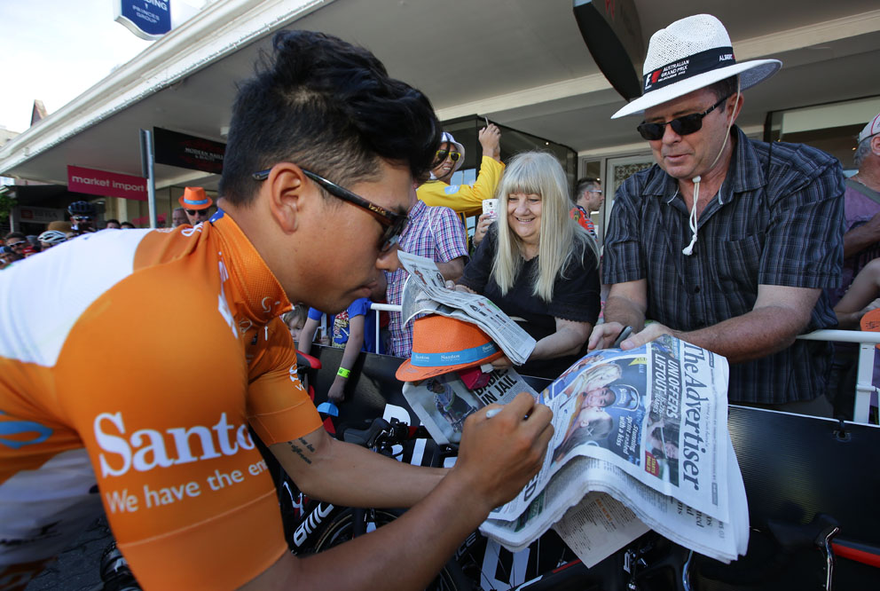 Stage2e-Ochre Jersey wearer Caleb Ewan signs autographs for the fans at race start