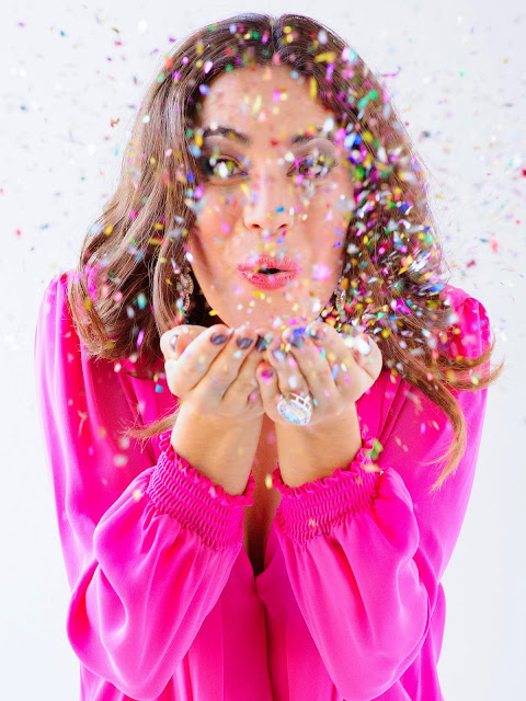 girl blowing confettit fashion editorial glitter christmas ootd pink