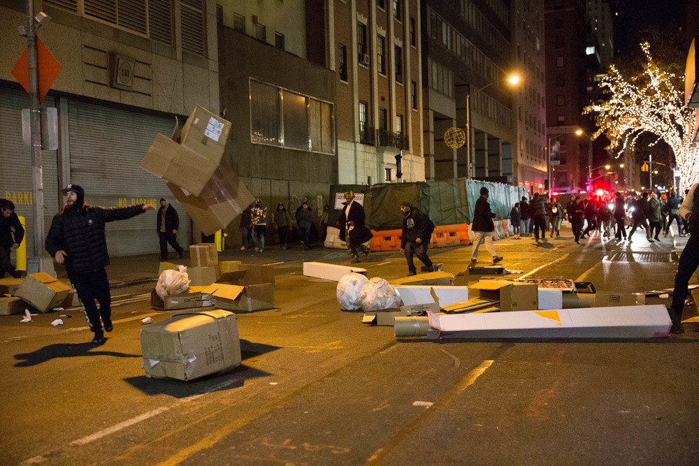 Protestors throw trash in the middle of the street, throw bottles, and knock over trash cans after the police used the LRAD system to scatter the crowds at around 2:41AM.