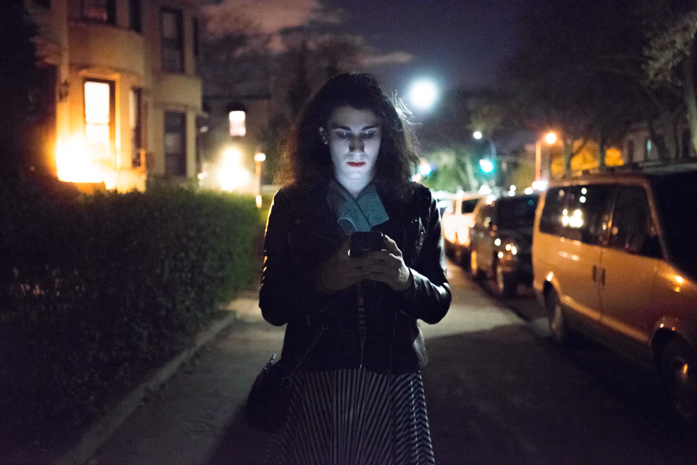 Ashley checks her phone as she walks through Bay Ridge to a friend's house. After coming out as transgender, her previous partner broke up with her. She hasn't contacted her since.