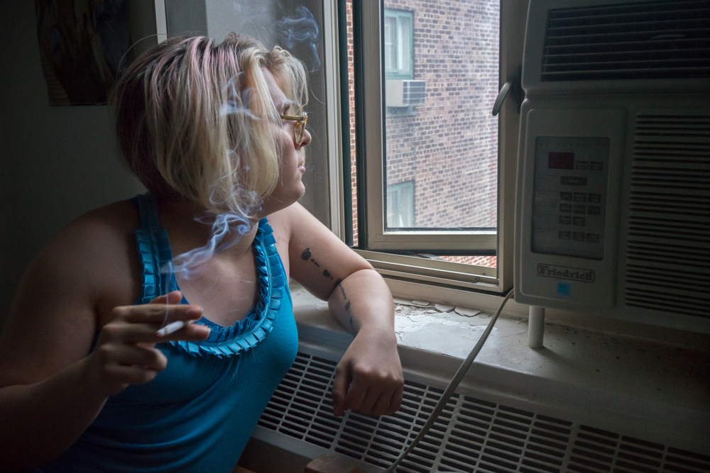 Kylie smokes a cigarette in her room in Stuyvesant Town, with the window open. She has lived in this apartment the majority of her life.