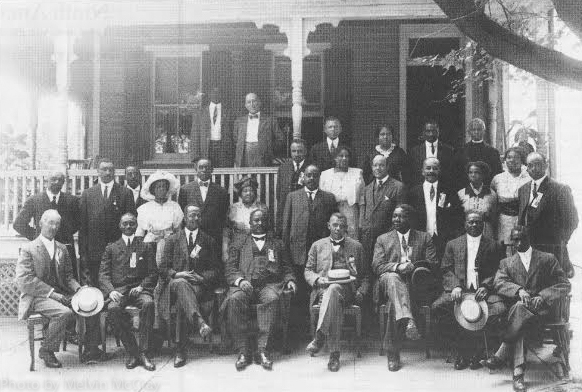 Booker T. Washington in a 1916 Princeton, New Jersey photo sitting in the center in front of what many believe to be 20 Green Street, a home slated for demolition in the 2016 version of the gentrification of the town's black community.  Bob Rivers '53 writes about it in the Articles Section. (Photo Courtesy of Princeton Historical Society)