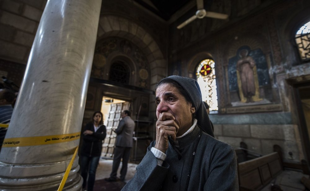 nun reacts as Egyptian security forces work at scene of explosion, Saint Peter and Saint Paul Coptic Orthodox Church,Cairo (Khaled Desouki/AFP/Getty Images)