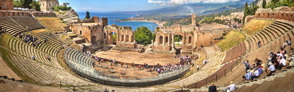 Taormina's Greek Theater in its natural setting with a splendid view toward the Calabrian coast. The theatre was renovated and expanded by the Romans, who inserted columns, statues and ingenious covers.