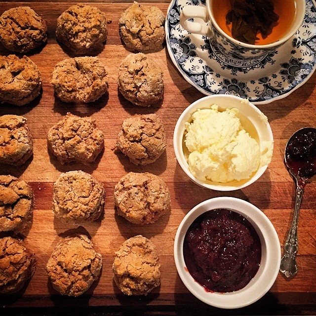 Homemade scones with plenty of native berry jam and whipped cream
