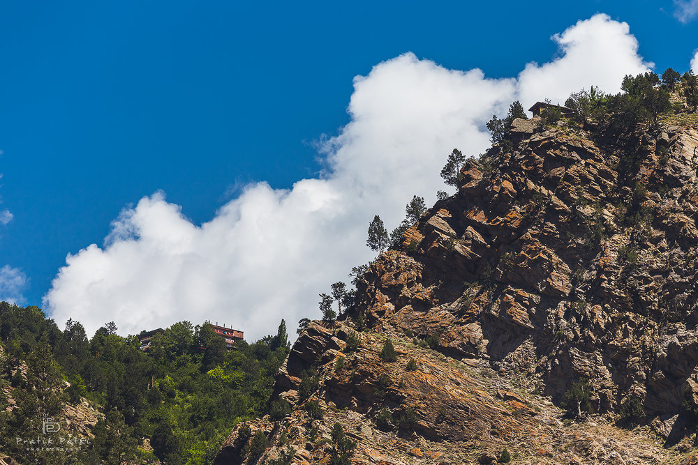 Rocky Neighbours   2 houses stand apart on a rocky ridge on the road to Pooh. The clouds and the blue sky just added to the setup