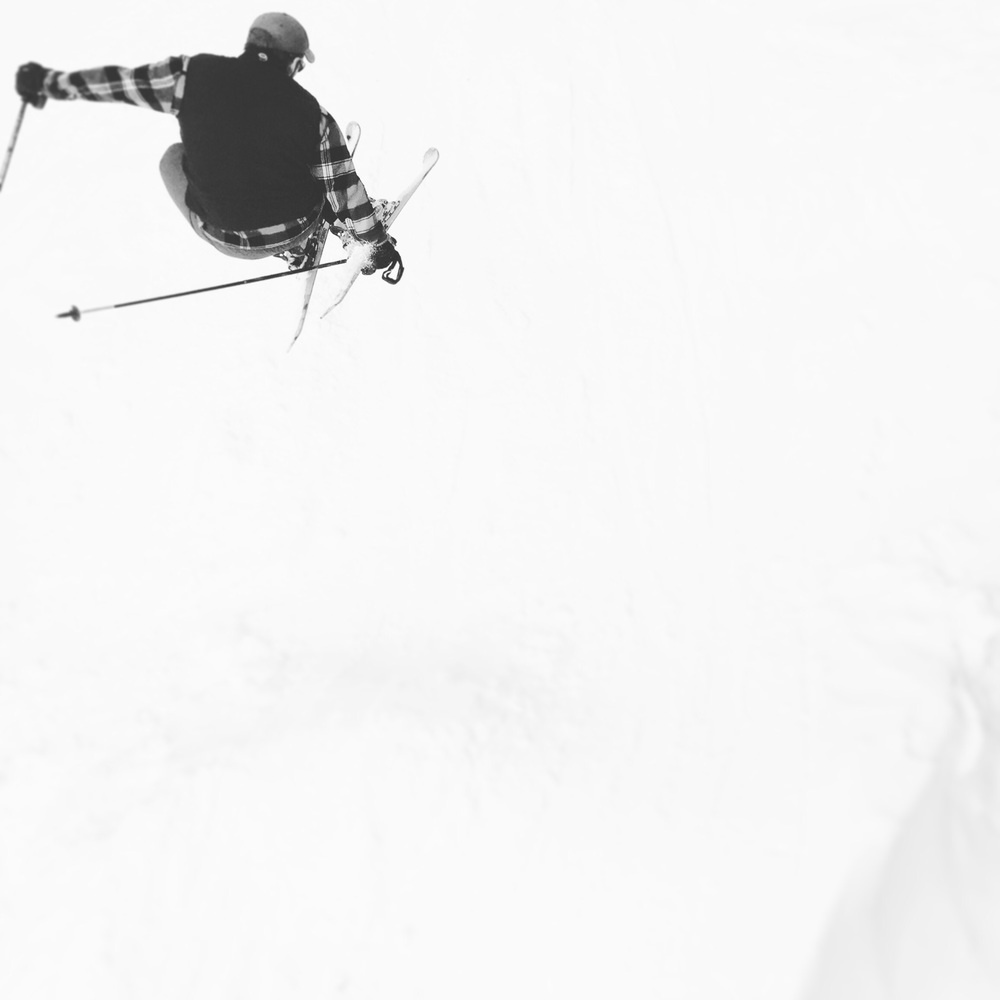 Photograph of skier jumping and in mid air.