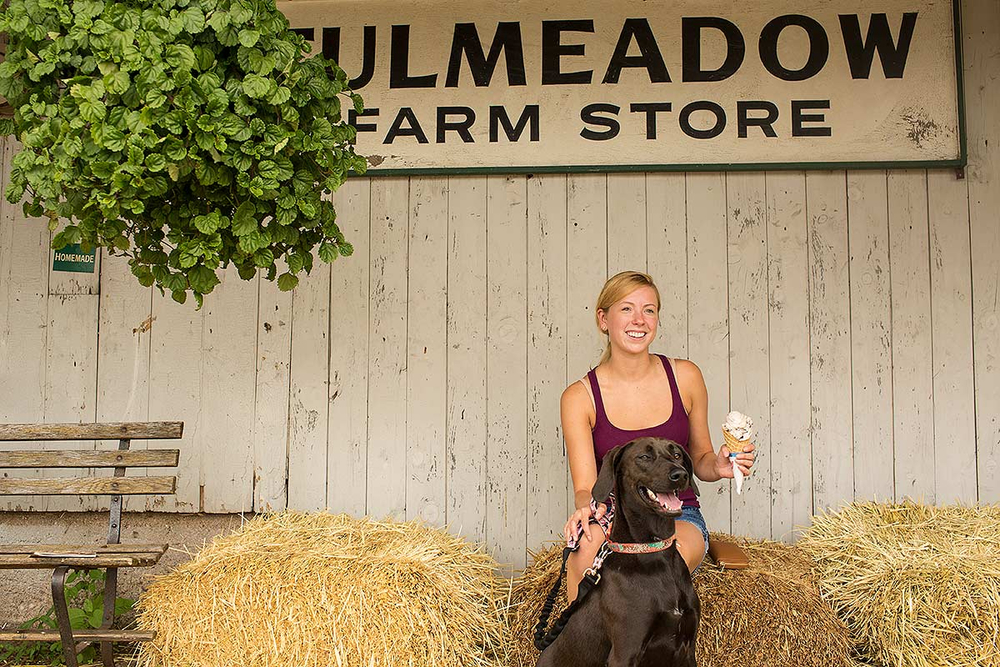 A woman and her dog enjoy ice cream outside a small town general store.