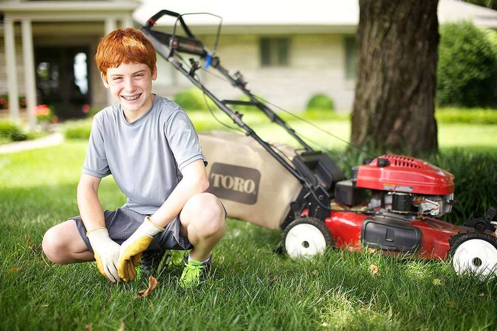 Young boy poses for a photograph advertising his lawn care business.