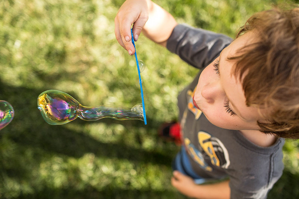Advertising image of a young boy blowing bubbles in the back yard.