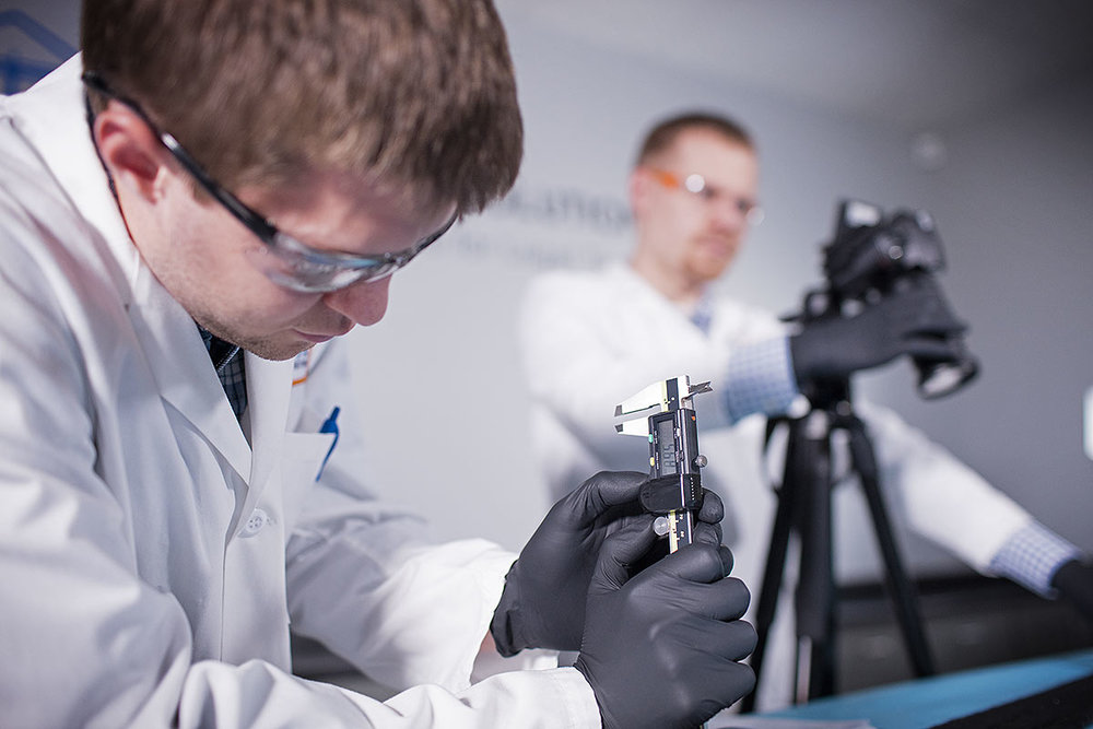 Scientists using instruments in a lab.