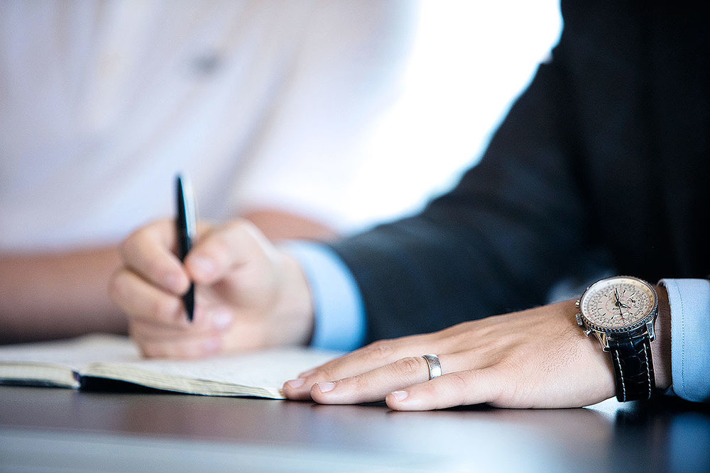 Stock image of a man writing in a meeting.