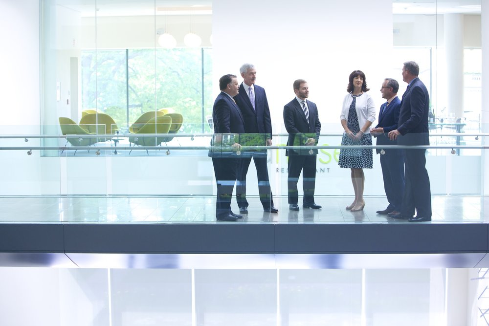 A financial team holds an impromptu meeting in a modern space.