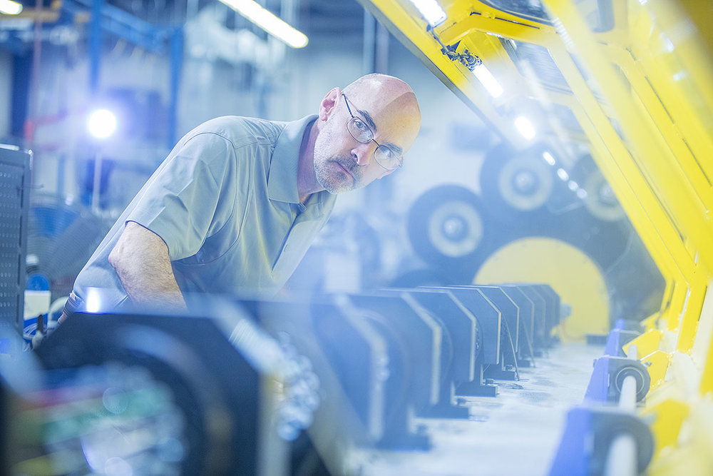 Manufacturing employee works on a modern automative process in a facility.