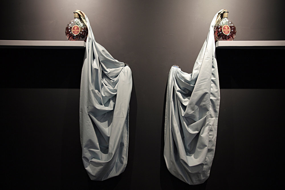 SWEAT (1), 2009, Two Remy Martin XO, bed sheet and two shelves, Dimension variable. In this work one bed sheet connects two bottles of Remy Martin XO Cognac, traveling from one bottle to the next through two holes in the gallery wall, the bed sheet travels behind the gallery wall.