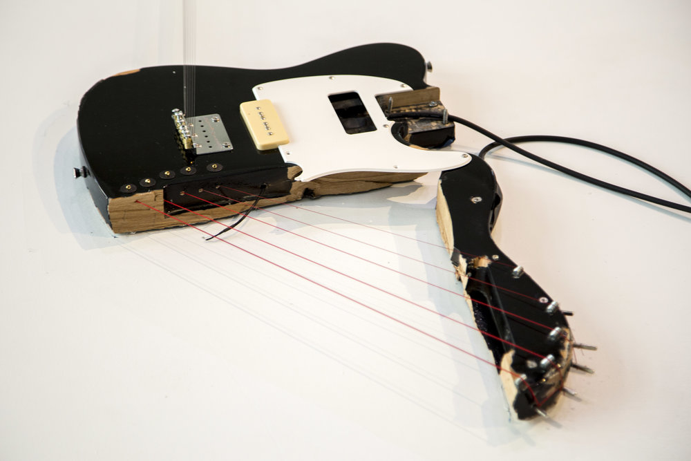 Melody of Certain Damage #4, 2018, detail, broken electric guitar, strings, microphone, screws and amplifier 134.5 x 40 x 2.5 in. Image by Loló Bonfanti
