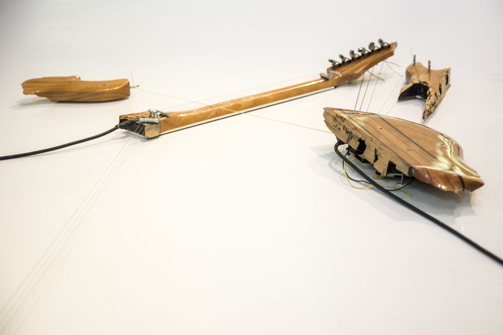 Melody of Certain Damage #2, 2018, detail, broken electric guitar, strings, microphone, screws and amplifier, 39 x 132 x 3 in. Image by Loló Bonfanti