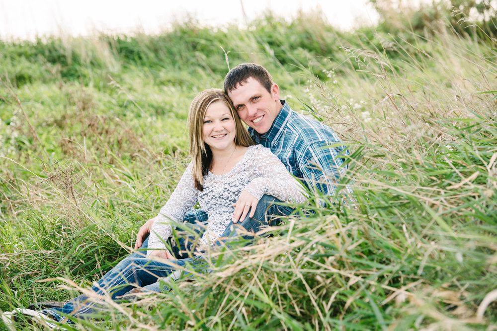 couple getting photos taken in tall natural grass.