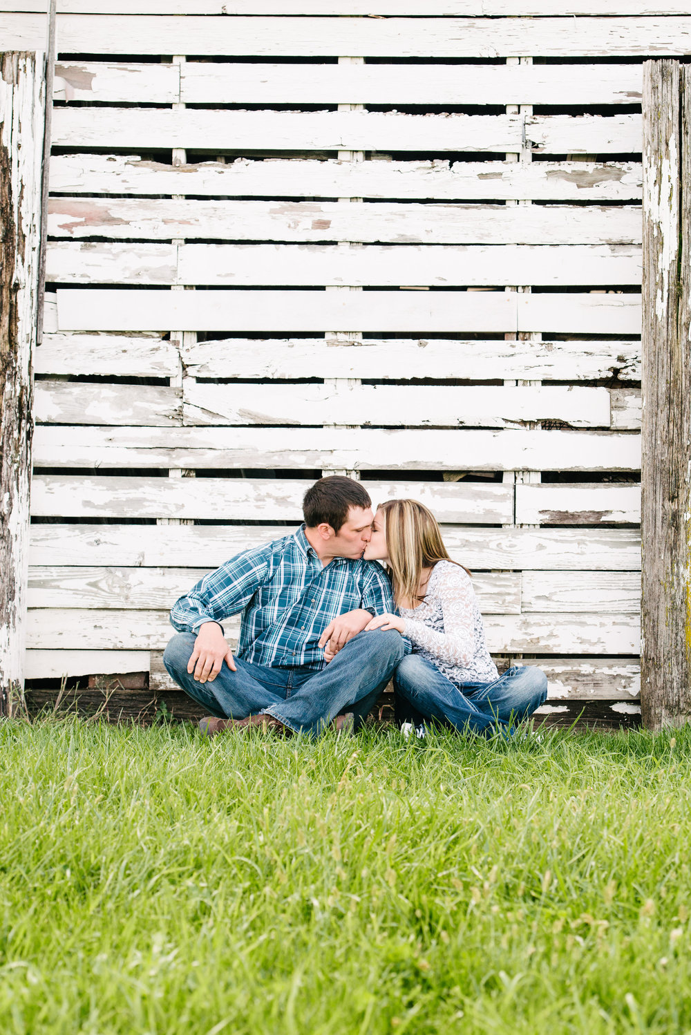 Kissing engagement photos by rustic barn.