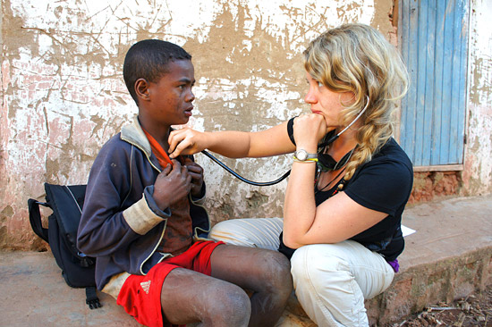 Emily Headrick of Emory University assessing the health of a young villager.   Photo by Carol Clark