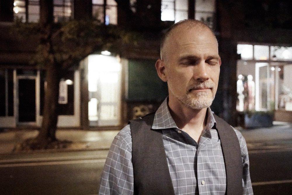 Craig Shepard listens on Bleecker Street in New York. Photo by Beth O'Brien.