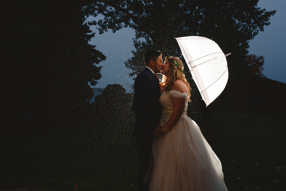 Arynn Photography Toronto Wedding Photographer, Couple standing in the rain and kissing under and umbrella at Rainbow Valley Wedding Barn in Caledon