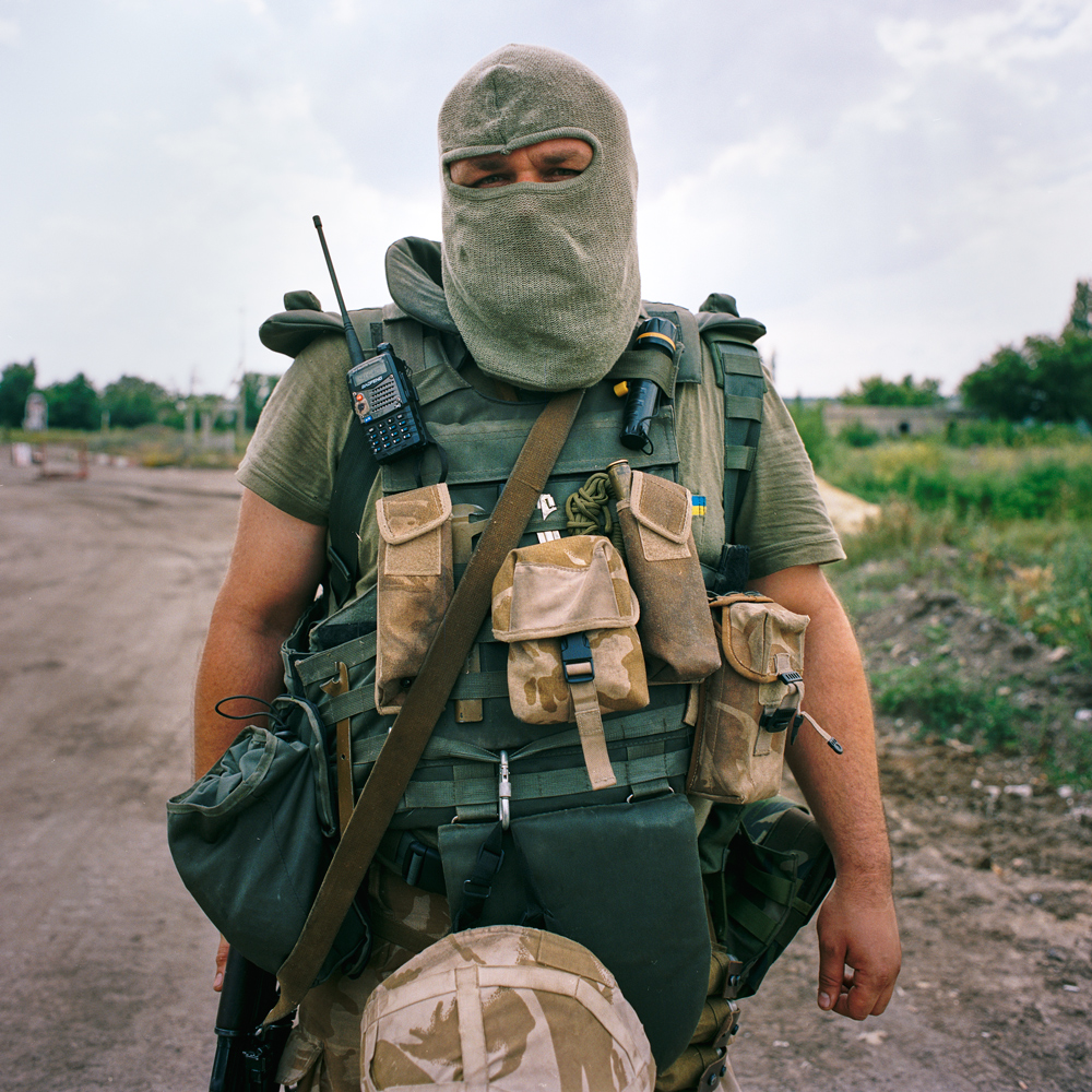 A masked soldier stands guard at a checkpoint in Karlovka, Donetsk region, Ukraine.