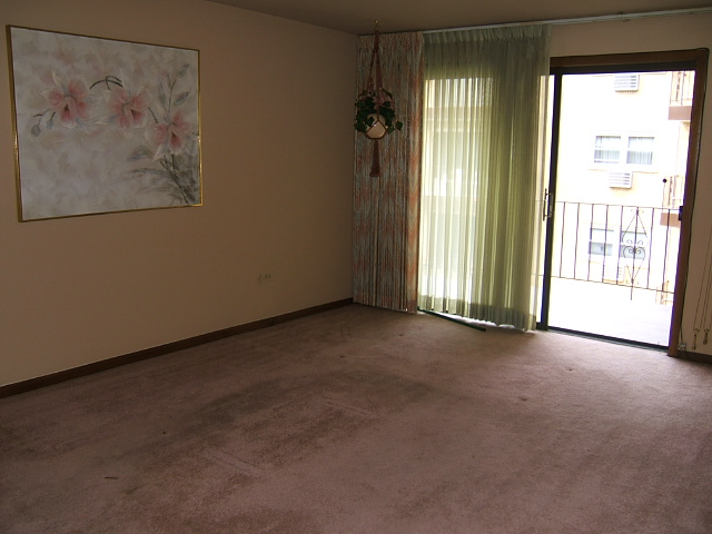 Living room before remodel. Several shades of mauve with green and floral curtains.