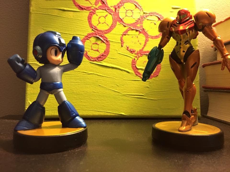 Mega Man (left) and Samus (right) amiibo figures face off in front some of homemade artwork, courtesy of my wife. They might both have arm cannons and be from the future, but they're quite different heroes.