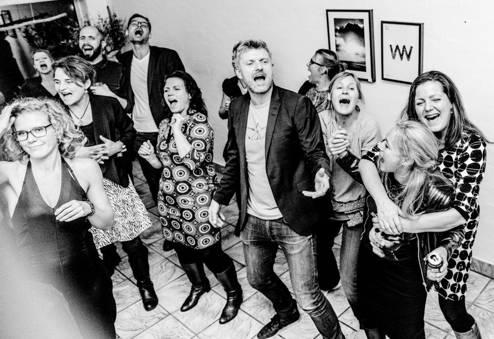 Sing along during the legendary Cowork Klitmøller Christmas party (2015). Starting left, in the foreground, Anna Thorsager; behind her (right), Anne Werner; behind her (left), Benthe Boesen; to her right, Troels Schwarz; on his right, Tommy Røsholt; on his right (in the foreground), Marianne Søstrøm Storm; behind to her right, Anette Balker; to her right, Tina Bach; to her left, Susanne Steinfath; to her left, Berit Hansen; in front of her, Therese Thomsen. Playing was Heine Thomsen. What a lovely bunch of people! The guy in the jacket – well, that's me.