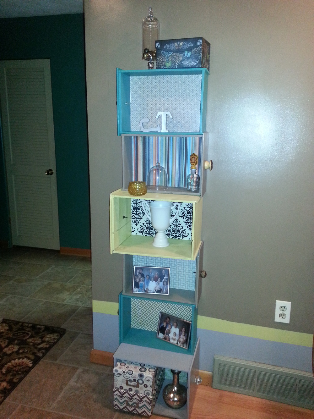 "A ""new"" shelf unit made from repurposed desk drawers, painted out in the colors of the room, lined with colorful papers and adorned with quirky, mismatched knobs.  Some coordinating storage boxes and a few new accessories compliment the accessories that were already in the room."