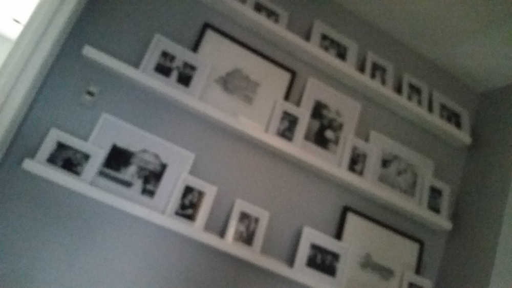 Custom made ledges were the idea of the homeowner, and provide a gallery wall for photos.  They now hold black and white photos of the couple's wedding.  As the family grows, the ledges can display children's artwork.