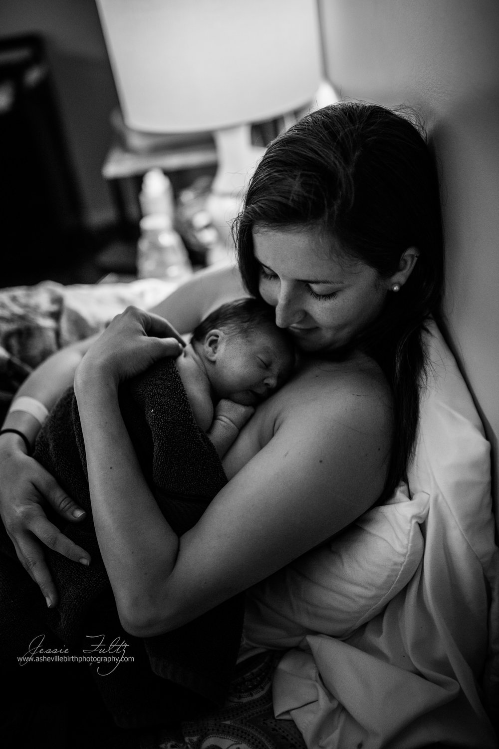 a black and white photo of a mom snuggling her baby right after birth
