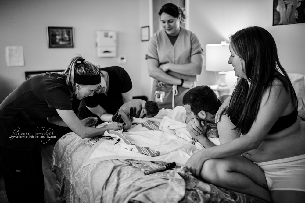 parents watch as midwives do newborn exam on their baby just after birth