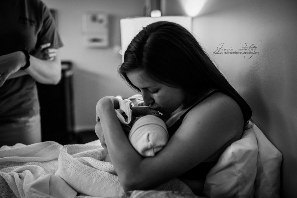 black and white picture of new mom kissing her baby just after birth