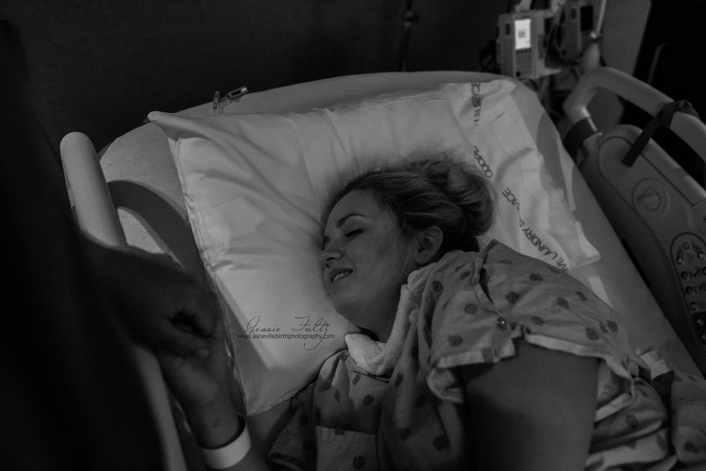 a laboring woman on a hospital bed smiling between contractions