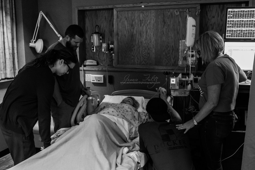 praying family surrounds a woman in labor