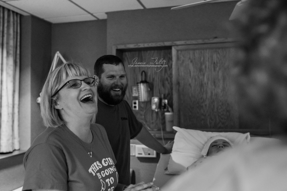 grandmother and laboring woman's husband laughing