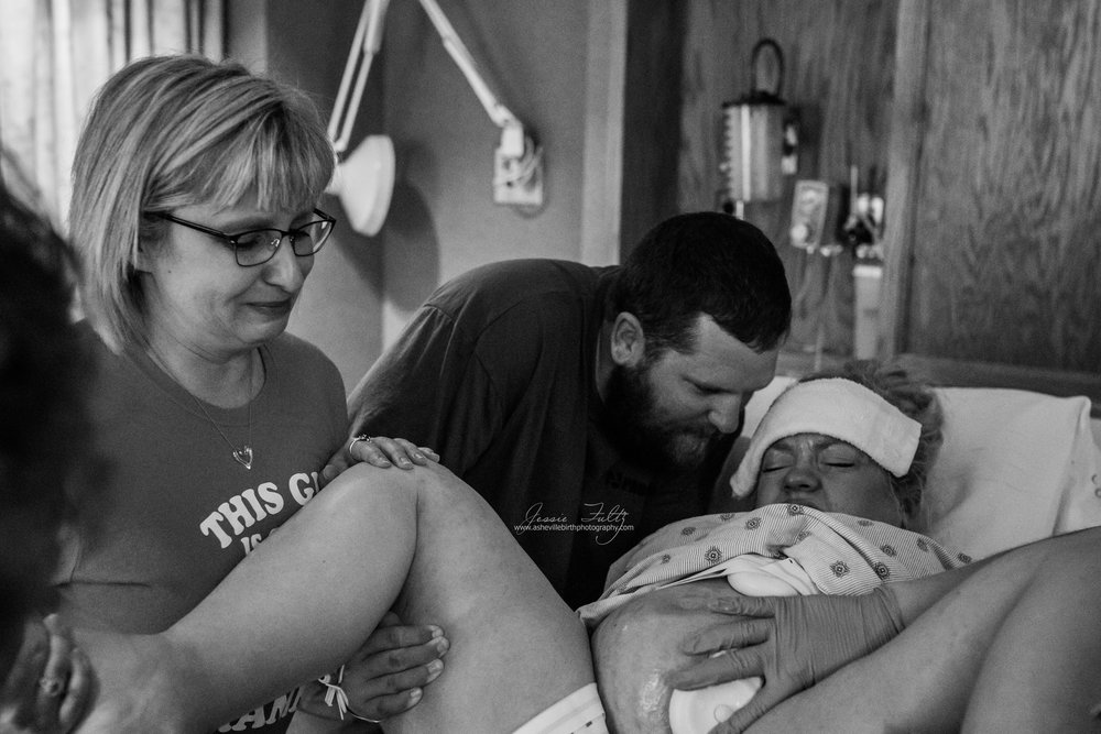 laboring woman pushing through a contraction while husband leans down to support and mom cries with joy