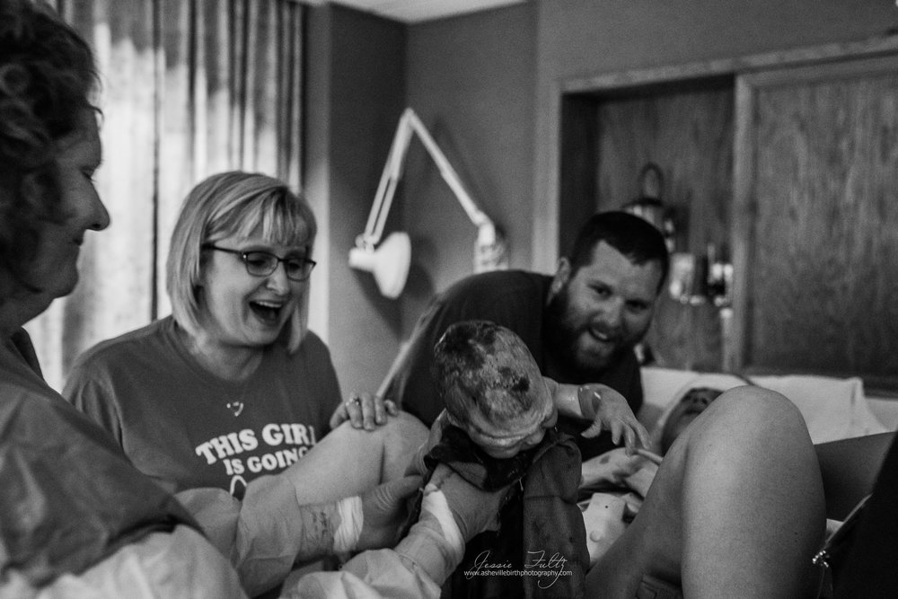 grandmother and dad smile as newborn baby is being handed to mom