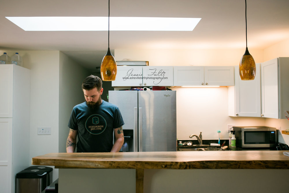 man in black t-shirt standing behind wooden-top bar in kitchen