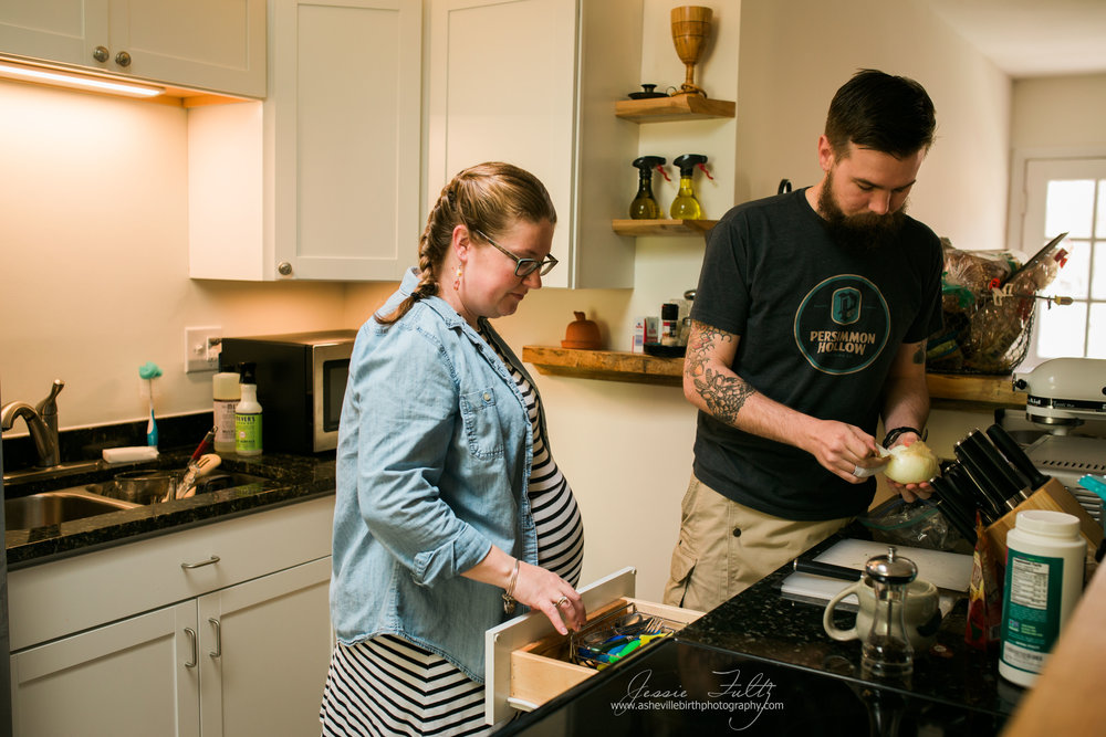 redheaded pregnant woman in striped dress looking in utensil drawer while husband peels an onion