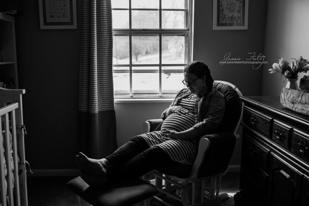 wide-angle black and white picture of pregnant woman in striped dress looking down at her belly sitting in a glider chair next to the window in her nursery
