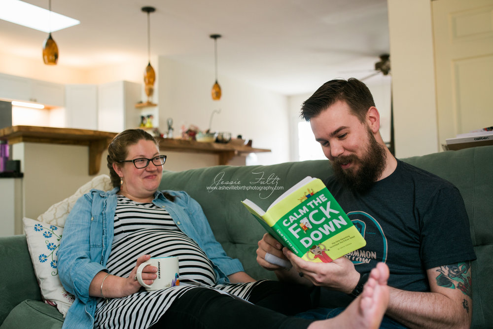 "pregnant wife and husband sitting on couch laughing as husband reads a book called ""Calm the F*ck Down"""